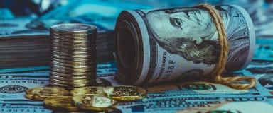 Um rolo dos dólares com as moedas no fundo do dispersado cem notas de dólar na luz azul imagem de stock