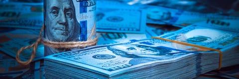 Um rolo dos dólares com um bloco dos dólares contra um fundo do dispersado cem notas de dólar na luz azul fotos de stock royalty free