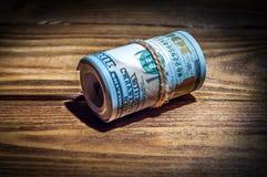 Um rolo dos dólares em uma tabela textured de madeira na obscuridade iluminada por um raio de luz imagem de stock royalty free