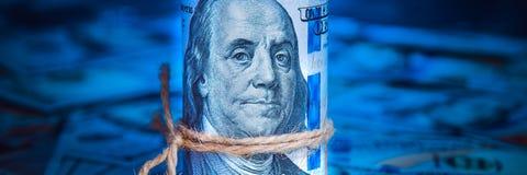 Um rolo dos dólares no fundo do dispersado cem notas de dólar na luz azul ilustração stock