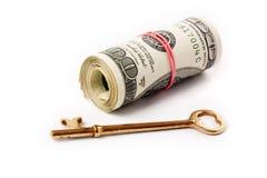 Um rolo dos dólares e da chave Fotografia de Stock Royalty Free