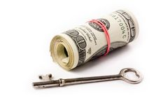 Um rolo dos dólares e da chave Fotos de Stock Royalty Free
