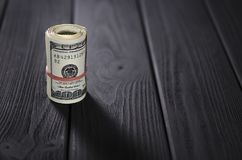 Um rolo grosso de cem cédulas do dólar amarrou um elástico vermelho encontra-se na tabela de madeira preta fotografia de stock