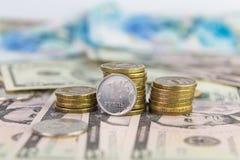 Um rublo contra de moedas empilhadas Fotos de Stock Royalty Free