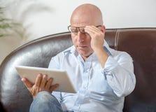 Um sênior olha uma tabuleta digital Foto de Stock Royalty Free