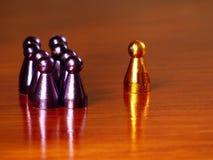 Um símbolo dourado na frente de um grupo de símbolos roxos em um fundo de madeira horizontal fotos de stock