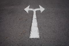 Um símbolo em dois sentidos da seta em uma estrada asfaltada preta Fotografia de Stock Royalty Free