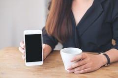 Um ` s da mulher entrega guardar e mostrar o telefone celular branco com a tela preta vazia do desktop com os copos de café na ta Imagens de Stock Royalty Free