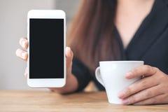 Um ` s da mulher entrega guardar e mostrar o telefone celular branco com a tela preta vazia do desktop com os copos de café na ta Imagens de Stock
