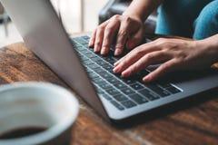 Um ` s da mulher entrega o trabalho e a datilografia no teclado do portátil com o copo de café na tabela de madeira foto de stock
