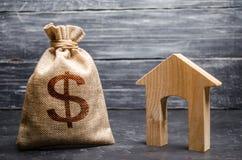 Um saco com dinheiro e uma casa com uma grande entrada Conceito da aquisição e do investimento dos bens imobiliários Empréstimo b imagem de stock
