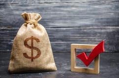 Um saco com dinheiro e uma marca de verificação vermelha de uma voz no fundo escuro O conceito dos serviços está incitando para l imagens de stock