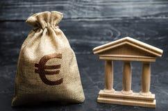 Um saco com euro- dinheiro e um banco ou uma construção do governo Depósitos, investimento no orçamento Concessões e subsídios Pa fotografia de stock royalty free
