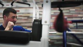 Um saco de encaixotamento da areia do homem no gym pela primeira vez Com expressão determinada da cara filme