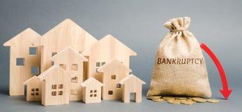 Um saco do dinheiro com a falência da palavra, uma seta da pena e as casas de madeira Leilão da falência Propriedade hipotecada C imagem de stock