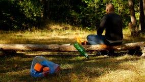 Um saco do lixo está encontrando-se na grama, um fogo está queimando-se, no fundo bebidas de uma pessoa uma bebida de uma garrafa video estoque