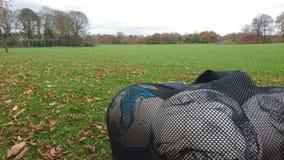 Um saco dos futebóis em um campo de ação Fotos de Stock