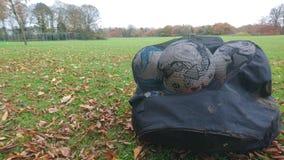 Um saco enlameado dos futebóis em um campo de ação da escola Fotos de Stock Royalty Free