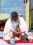 Um sadhu que lê o roteiro religioso no banco do rio do kshipra no mela 2016 do kumbh do kha, Ujjain, Índia Imagens de Stock Royalty Free