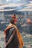 Um Sadhu que presta atenção a uma cremação Fotos de Stock Royalty Free