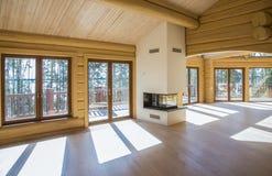 Um salão espaçoso em uma casa de madeira com as grandes janelas na madeira imagem de stock royalty free