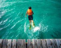 Um salto da baía da ponte de madeira ao mar para nadar imagem de stock
