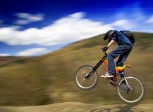 Um salto do motociclista da montanha imagem de stock