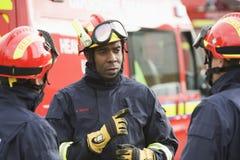 Um sapador-bombeiro que dá instruções a sua equipe imagens de stock royalty free