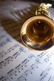 Um saxofone que encontra-se na partitura Fotos de Stock Royalty Free