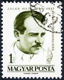 Um selo do cargo impresso em HUNGRIA mostra que um retrato de Mate Zalka dedicou ao 65th aniversário do nascimento de Mate Zalka fotos de stock royalty free