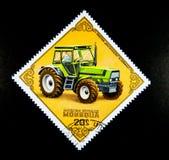 Um selo impresso em Mongólia mostra uma imagem de um homem que conduz do `` em um ` W trator DEUTZ DX-230 ` De Alemanha Imagens de Stock Royalty Free
