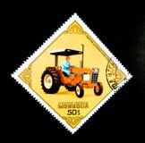 Um selo impresso em Mongólia mostra uma imagem de um homem que conduz em um ` dos EUA do international 884 do trator do ` Imagem de Stock
