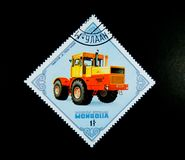 Um selo impresso em Mongólia mostra uma imagem de um homem que conduz em um ` U do trator K 7100 do ` S S R do ` Foto de Stock