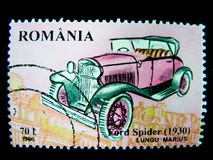 Um selo impresso em Romênia mostra uma imagem de um carro cor-de-rosa do clássico de Ford Spider 1930 Fotos de Stock Royalty Free