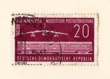 Um selo oriental vermelho velho com uma imagem de um bombardeiro de jato e de um transporte railway do trem fotos de stock royalty free