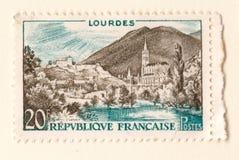 Um selo postal francês velho com uma imagem de lourdes que mostra a montanha e o lago da vila da igreja imagens de stock royalty free
