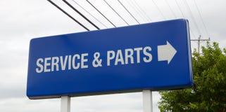Um serviço do concessionário automóvel e um sinal das peças Fotografia de Stock Royalty Free