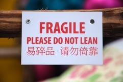 Um signage de advertência frágil enviado em um polo de madeira imagens de stock royalty free