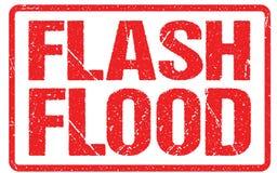 Um sinal de aviso da estrada contra um céu tormentoso com área de inundação repentina das palavras, aviso da inundação ilustração stock