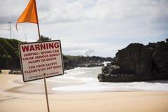 Um sinal de aviso na praia imagens de stock