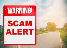 Um sinal de aviso que adverte sobre Scam na estrada fotografia de stock