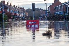 Um sinal de Cosed da estrada em uma estrada inundada Imagens de Stock Royalty Free