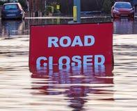 Um sinal de Cosed da estrada em uma estrada inundada Fotografia de Stock Royalty Free