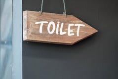 Um sinal de madeira do toalete que pendura por uma corda imagens de stock royalty free