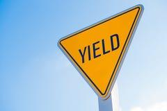 Um sinal de rendimento amarelo contra um fundo do céu azul fotografia de stock royalty free
