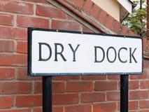 Um sinal de rua preto e branco que diz a doca seca com backgro do tijolo foto de stock royalty free