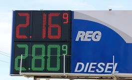 Um sinal do posto de gasolina indica preços de gás Imagens de Stock Royalty Free