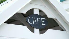 Um sinal em uma casa do jogo do ` s das crianças, uma inscrição de um café, em uma placa preta escrita no palavra-café branco do  vídeos de arquivo