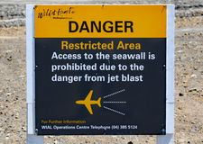 Um sinal na extremidade da pista de decolagem do aeroporto em Wellington, em Nova Zelândia, na advertência dos perigos da explosã fotografia de stock royalty free