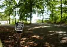 Um sinal por uma estrada de floresta Imagem de Stock Royalty Free